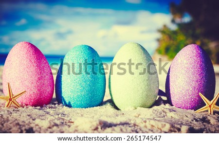 Colorful easter eggs on ocean beach  - stock photo
