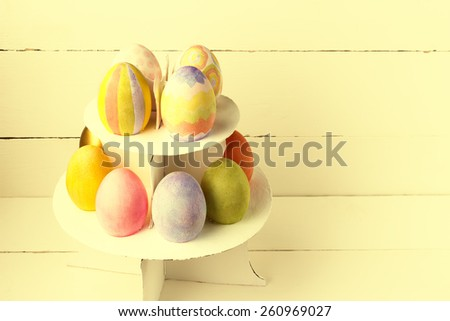 Colorful Easter eggs on stand. Toned vintage effect - stock photo