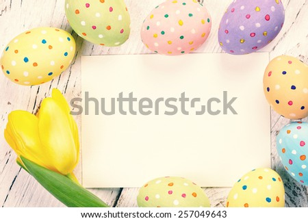 Colorful Easter eggs, tulip and blank card on wooden background - stock photo