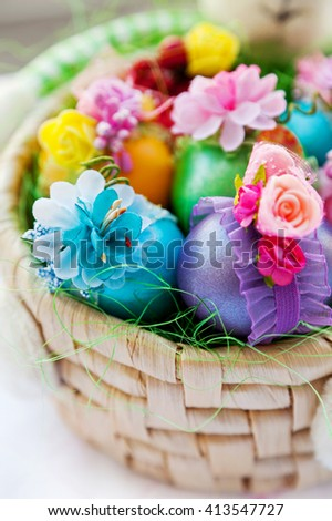 Colorful Easter eggs with ornaments in rabbit basket  - stock photo