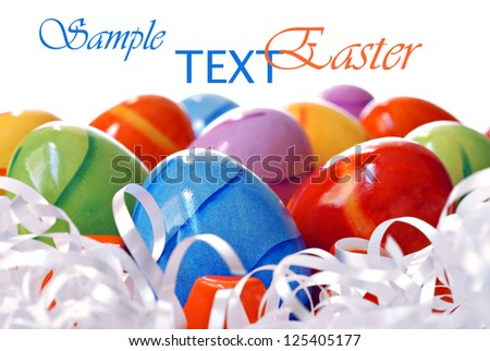 Colorful Easter eggs with ribbon on white background with copy space.  Macro with shallow dof.  Selective focus on blue egg. - stock photo
