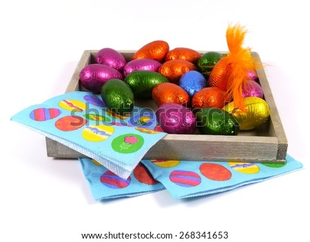 Colorful eggs of chocolate with an orange feather on blue easter napkins over white - stock photo