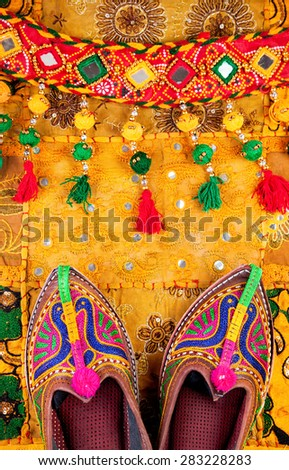 Colorful ethnic shoes and gypsy belt on yellow Rajasthan cushion cover on flea market in India - stock photo