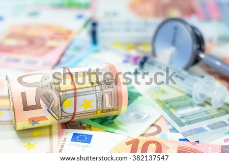 Colorful euro currency with blurry stethoscope and syringe costs for the medical insurance,Focus on number 50 of currency roll - stock photo