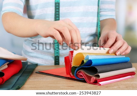 Colorful fabric samples in female hands on light blurred background - stock photo
