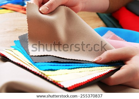 Colorful fabric samples in female hands on wooden table background - stock photo