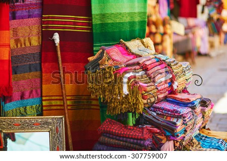 Colorful fabrics and carpets for sale on a street in Medina of Chefchaouen, Morocco, small town in northwest Morocco known for its blue buildings - stock photo