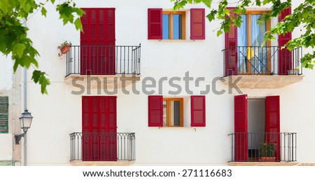 Colorful facade of spanish style old house surrounded by trees. - stock photo