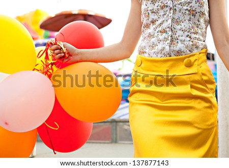 Colorful faceless view of a young woman visiting an amusement park arcade, holding balloons next to an attraction ride. - stock photo