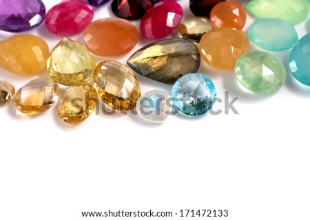 Colorful faceted real gemstones on the white background. Mix of different shapes and colors. Precious and semiprecious gems: ruby, amethyst, moonstone, labradorite, citrine, topaz, quartz and more. - stock photo