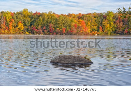Colorful Fall foliage reflecting off the waters of Burr Pond State Park in Torrington Connecticut. - stock photo