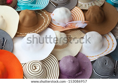 Colorful female summer hats lie on the counter - stock photo
