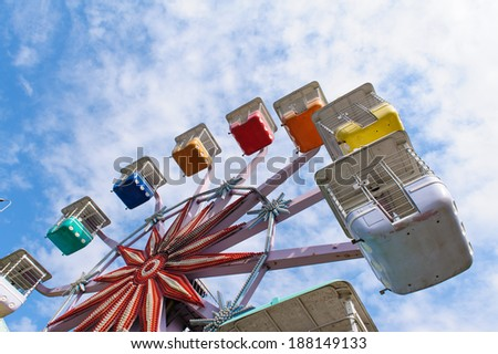 colorful ferris wheel in the playground against the blue sky - stock photo