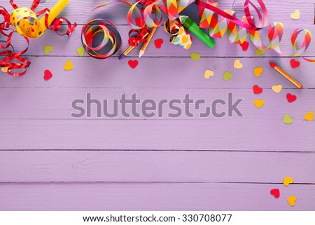 Colorful festive party border and background with with vibrant multicolored streamers, matches and confetti on a rustic lilac wood background with copyspace for your greeting or invitation - stock photo