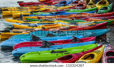 Colorful fiberglass kayaks tethered to each other - stock photo