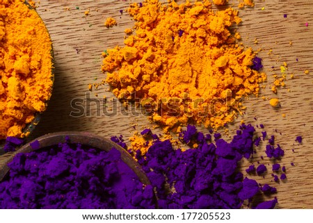 Colorful, finely powdered Indian pigments. Complementary colours: purple and yellow. - stock photo