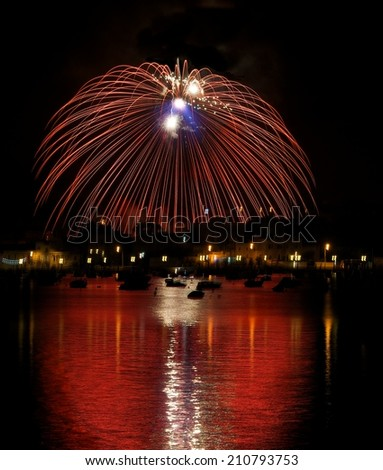 Colorful fireworks explosion with marvellous reflection on the sea, 4 of July, Independence day, explode, fireworks with village silhouette in background in Birzebugga, Malta.Malta fireworks festival  - stock photo