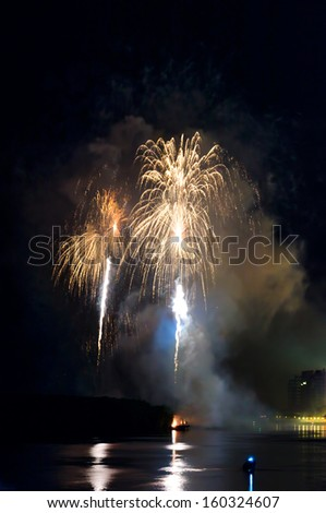 Colorful fireworks. Fireworks are a class of explosive pyrotechnic devices used for aesthetic and entertainment purposes. Visible noise due to low light, soft focus, shallow DOF, slight motion blur - stock photo