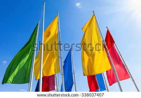 Colorful flags fluttering on the blue sky background - stock photo