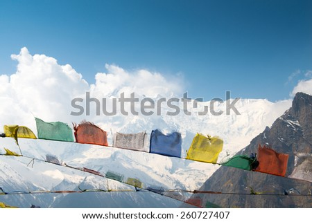 Colorful flags on a Annapurna Circuit - most popular tourists trek in Himalayan mountain massive in Nepal. - stock photo