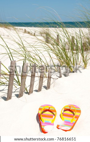 colorful flip flops on sand dune - stock photo