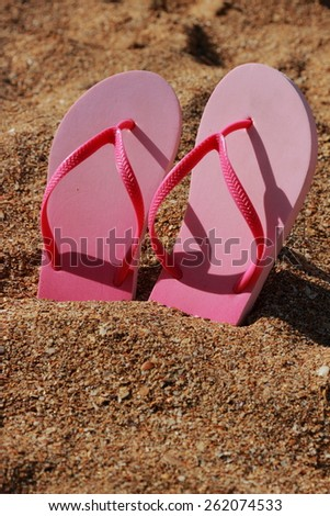 Colorful flip flops on the sand at the beach in summer sunny day - stock photo