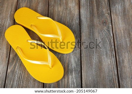 Colorful flip-flops on wooden background - stock photo