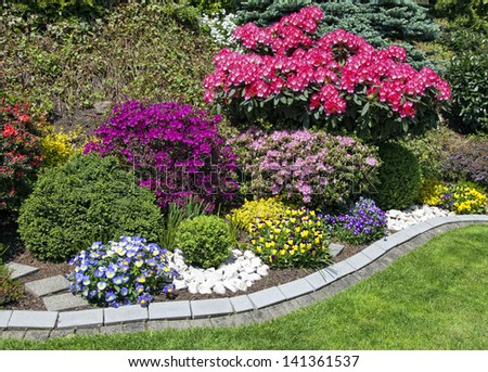 colorful flower garden with lots of blooming flowers - stock photo