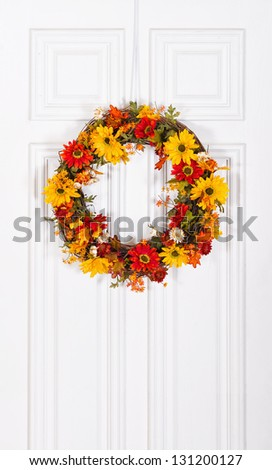 Colorful flower wreath hanging on white wood door - stock photo