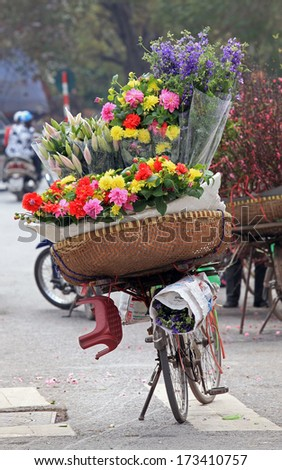Colorful flowers on a vendor bicycle on Hanoi street, Vietnam. - stock photo