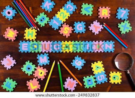 Colorful foam puzzle letters with pencils and lens on wooden background, education concept - stock photo