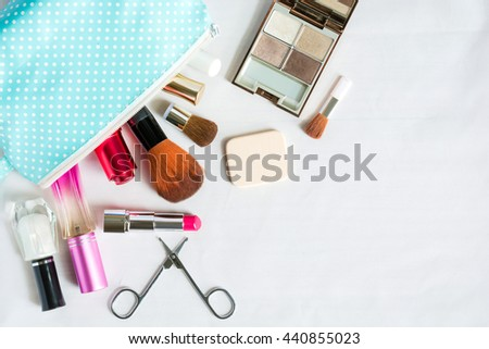 Colorful frame with various makeup products on white background with copy space, bag, lipstick ,powder, perfume, scissors, fingernail paint, brush. The concept cosmetics makeup, beauty, Travel. - stock photo