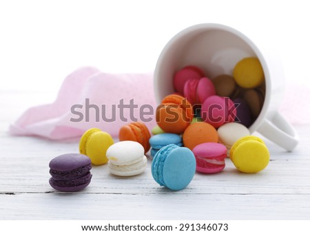 Colorful French Macarons on the floor with a white cup for background - stock photo