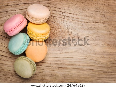 Colorful French Macarons on wooden background - stock photo