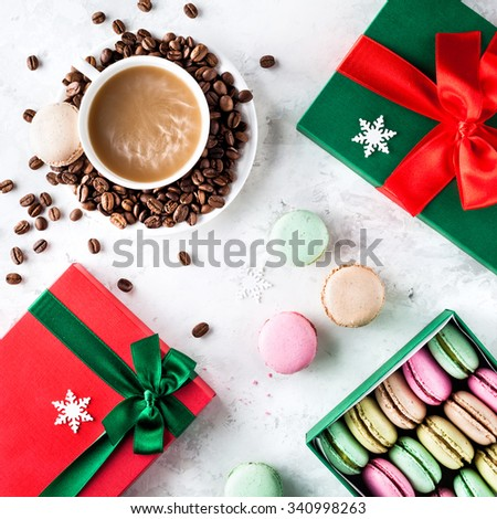 Colorful French macarons with cup of coffee and present Christmas boxes on white background - stock photo