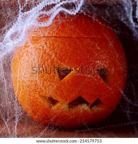 Colorful fresh orange Halloween lantern carved with a traditional jack-o-lantern face covered in spooky eerie cobwebs for a creative rustic handicraft Halloween background - stock photo
