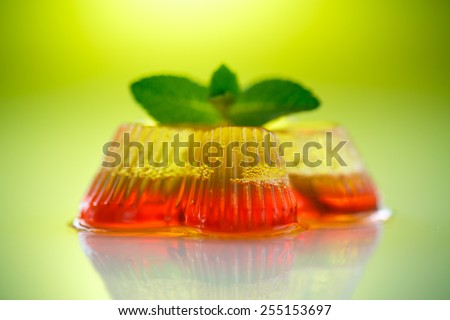 colorful fruit jelly sweets on a green background - stock photo