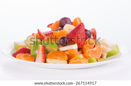 Colorful fruit salad heaped on a white plate, on light background - stock photo
