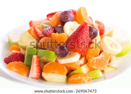 Colorful fruit salad heaped on white plate - stock photo