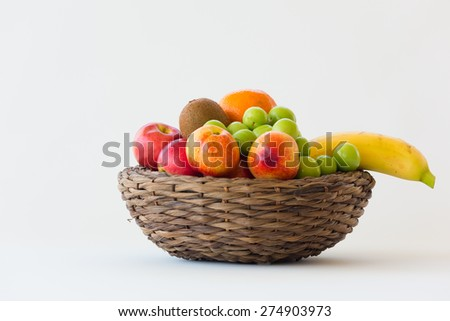 Colorful fruits in a wicker basket isolated on white background - stock photo