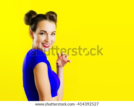 Colorful funny beautiful girl represents a small cat clutches. Woman with bright makeup and bright blue top hairstyle of woman with cat or mouse ears having fun. On yellow background not isolated - stock photo