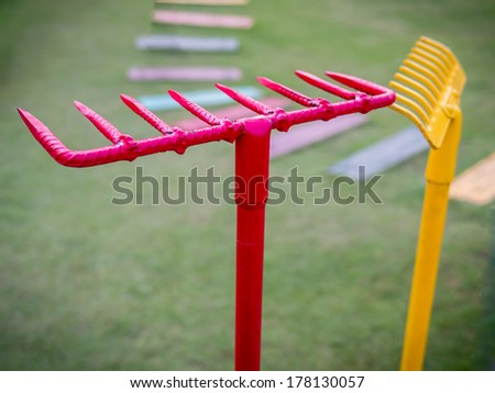 Colorful garden (steel rake) accessories  on green grass background - stock photo
