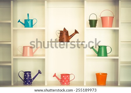 colorful gardening tools on white shelf - bucket, watering can  - stock photo