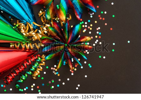 colorful garlands, streamer, party hats and confetti on black. festive background with carnival decoration - stock photo