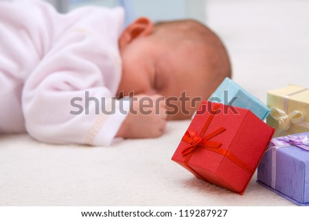 Colorful gift boxes with sleeping baby in background - stock photo