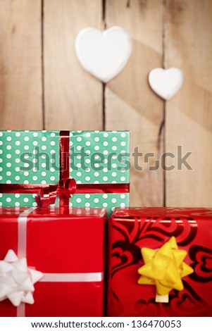 colorful gift packages in front of a wooden background with two heart hanged.shallow depth of field.focus is on green package - stock photo