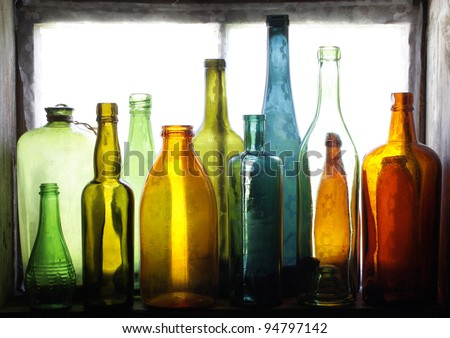 Colorful glass bottles on windowsill - stock photo
