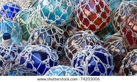 Colorful glass fishing floats with netting. Glass floats provided buoyancy, but were sometimes lost and washed ashore. - stock photo