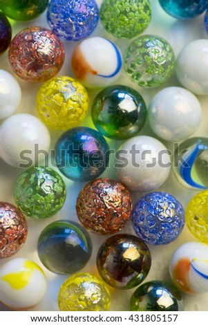 colorful glass marble balls on white wood background - stock photo