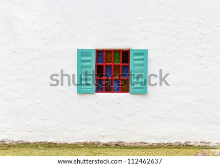 Colorful glass window on white wall. - stock photo